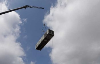 Big crane moving industrial HVAC unit.